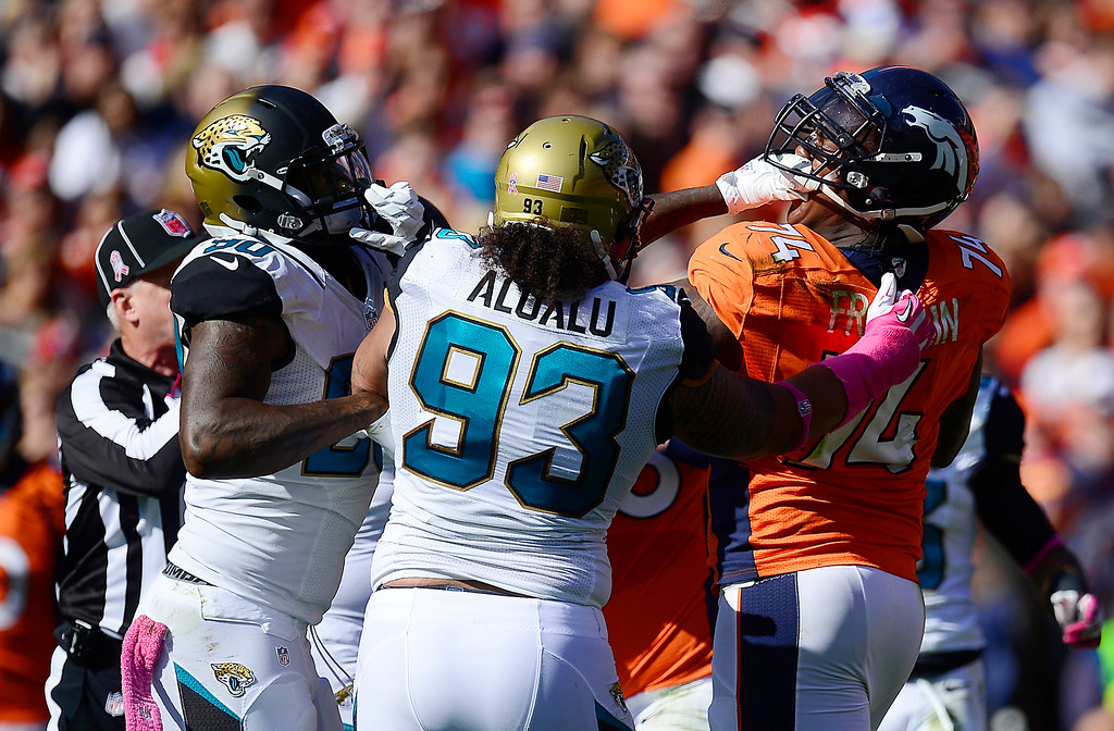 . Jacksonville Jaguars defensive end Andre Branch (90) grabs Denver Broncos tackle Orlando Franklin (74) by the face mask in the first quarter.  (Photo by AAron Ontiveroz/The Denver Post)