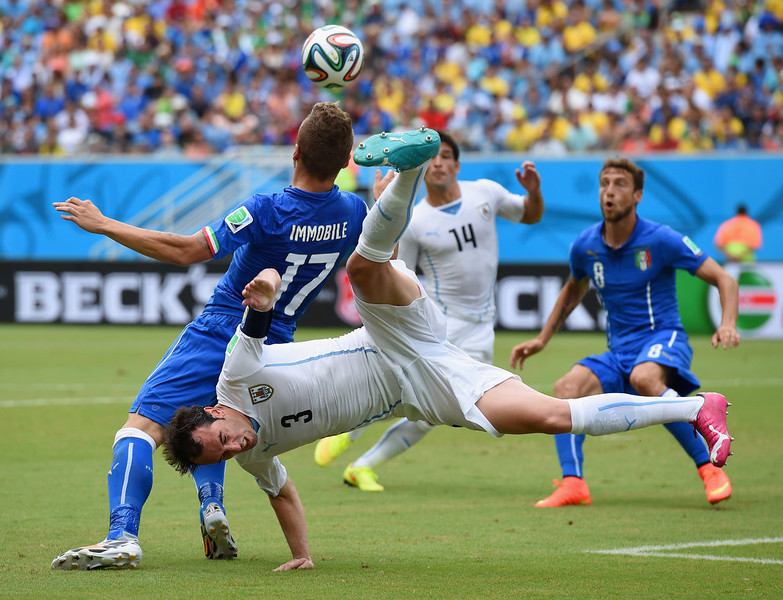. Diego Godin of Uruguay and Ciro Immobile of Italy compete for the ball during the 2014 FIFA World Cup Brazil Group D match between Italy and Uruguay at Estadio das Dunas on June 24, 2014 in Natal, Brazil.  (Photo by Matthias Hangst/Getty Images)