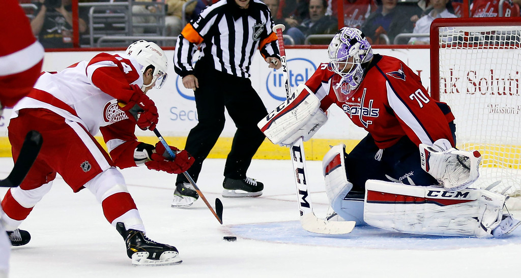 . Detroit Red Wings center Gustav Nyquist (14), from Sweden, works the puck before scoring a goal past Washington Capitals goalie Braden Holtby (70) in the second period of an NHL hockey game, Wednesday, Oct. 29, 2014, in Washington. (AP Photo/Alex Brandon)