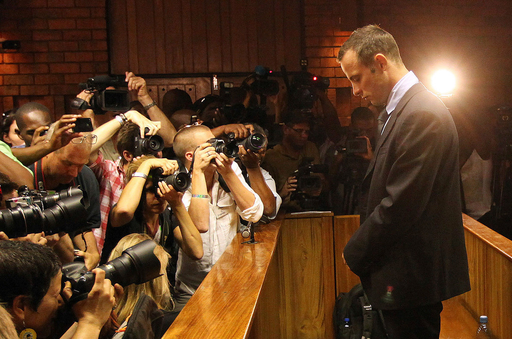 . n this Friday, Feb. 22, 2013 file photo photographers take photos of Olympic athlete Oscar Pistorius as he stands in the dock during his bail hearing at the magistrates court in Pretoria, South Africa.(AP Photo/Themba Hadebe)