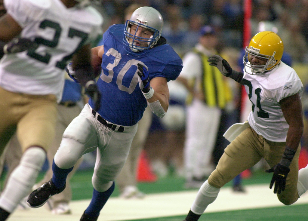 . Detroit Lions fullback Cory Schlesinger (left, #30) runs for a first down on a fake punt play as he is pursued by Green Bay Packers safety Chris Akins (#31) in the first quarter, Thursday, November 22, 2001, in Pontiac, Mich.  The Lions lost to the Packers, 29-27.