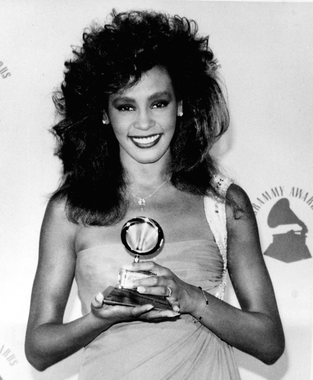 ". Whitney Houston poses with her Grammy backstage at the Grammy Awards in Los Angeles, Ca., Feb. 26, 1986.  Houston won best female pop vocal performance for her song ""Saving All My Love For You.\""  (AP Photo/Lennox McLendon)"