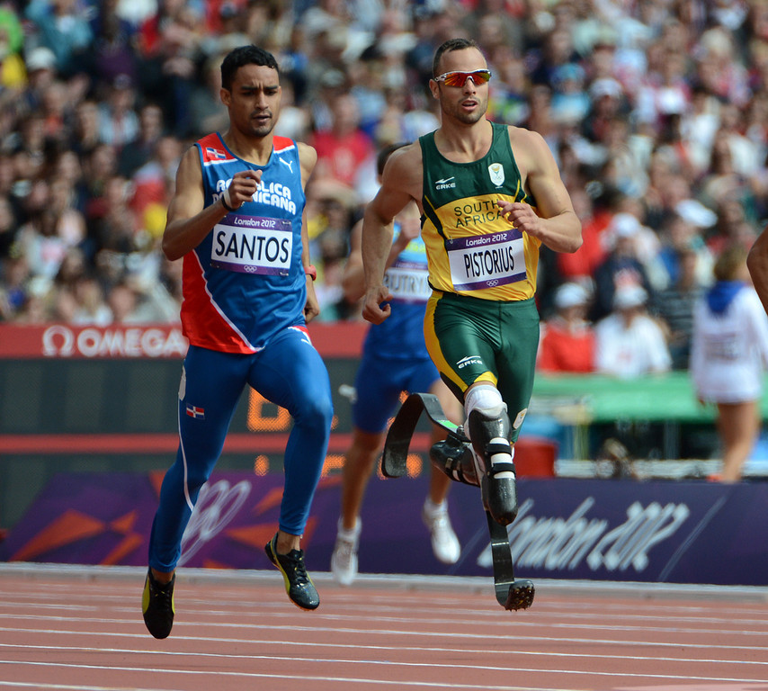 . South Africa\'s Oscar Pistorius, center, runs next to Dominican Republic\'s Luguelin Santos in their Men\'s 400m heat at the Olympic Stadium for the London 2012 Olympics in London, England on Saturday, Aug. 4, 2012.  (Nhat V. Meyer/Mercury News)