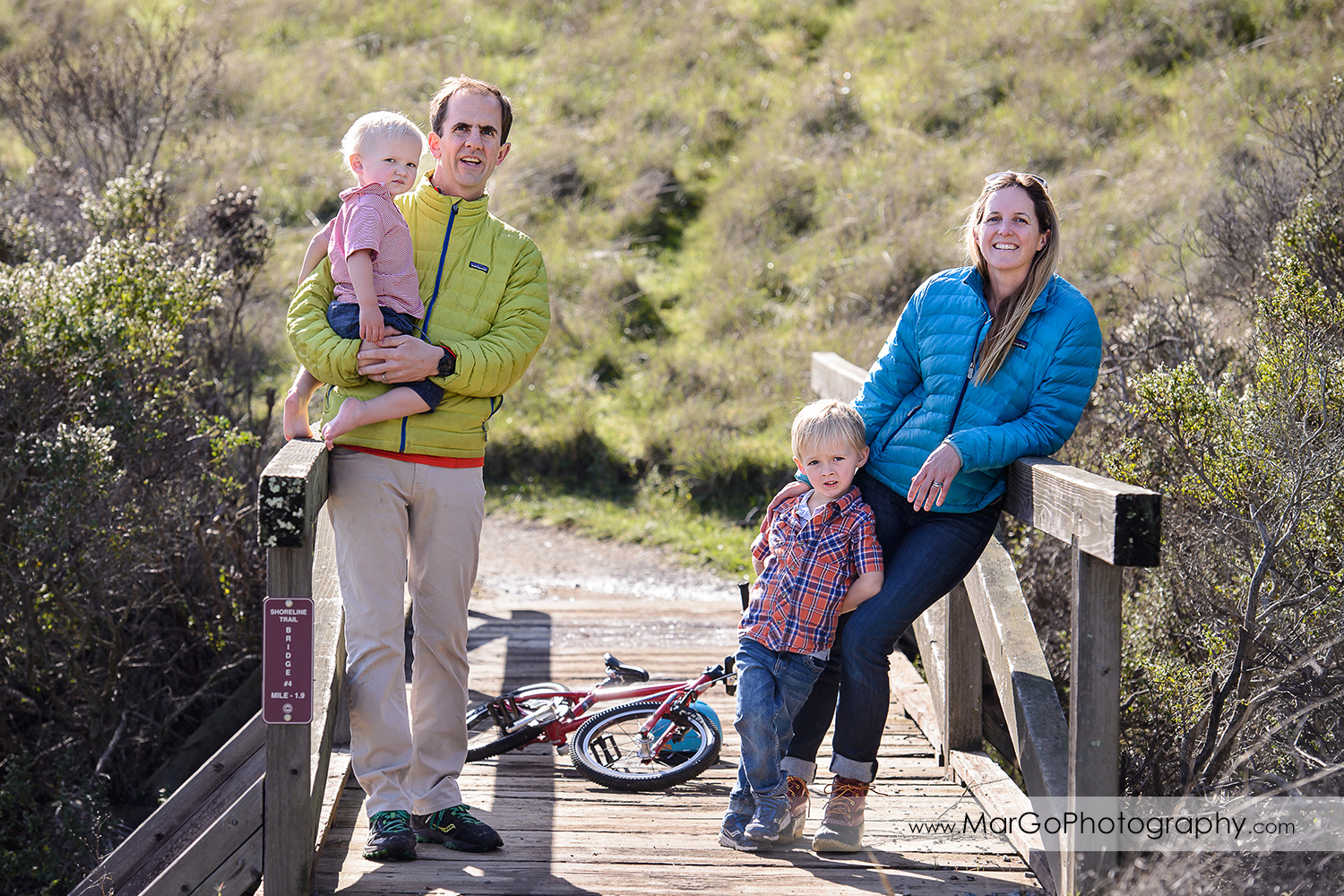 full body portrait of family of four standing on the wooden bridge during outdoor family session at San Raeael China Camp SP