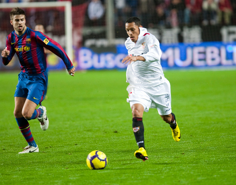 Adriano with the ball pursued by Pique. Spanish Cup game between Sevilla FC and FC Barcelona, Ramon Sanchez Pizjuan stadium, Seville, Spain, 13 January 2010
