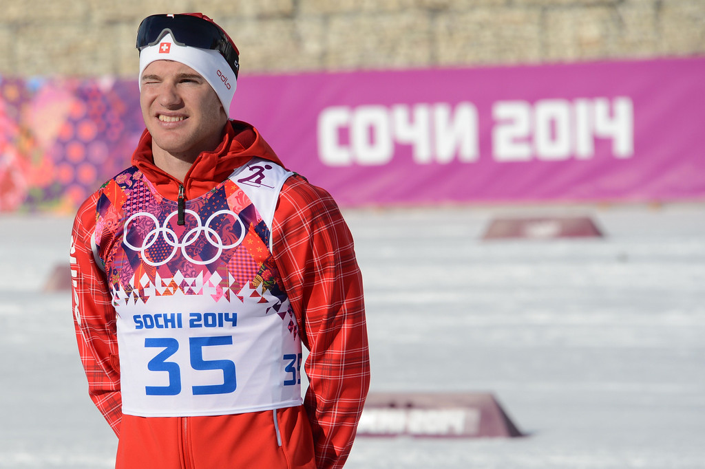 . Gold medalist Switzerland\'s Dario Cologna celebrates on the podium in the Men\'s Cross-Country Skiing 15km Classic Flower Ceremony at the Laura Cross-Country Ski and Biathlon Center during the Sochi Winter Olympics on February 14, 2014 in Rosa Khutor near Sochi. AFP PHOTO / KIRILL KUDRYAVTSEV/AFP/Getty Images