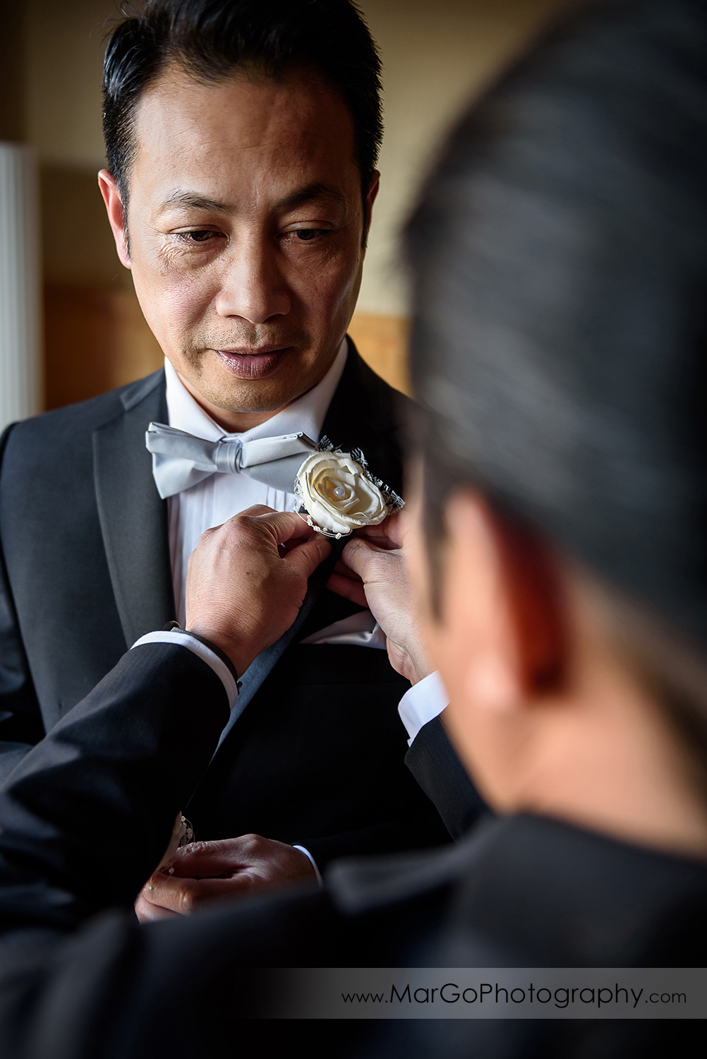 groom putting on a boutonniere at Hilton San Francisco Airport Bayfront in Burlingame
