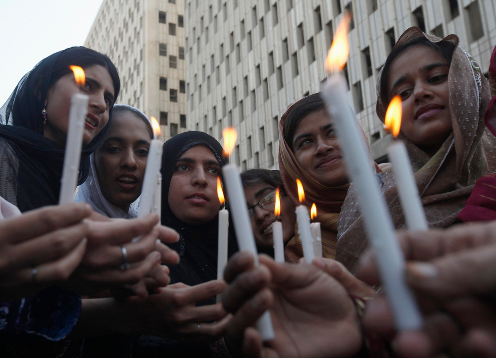 . Women light candles while taking part in a rally to commemorate International Women\'s Day in Karachi on March 8, 2013. REUTERS/Athar Hussain