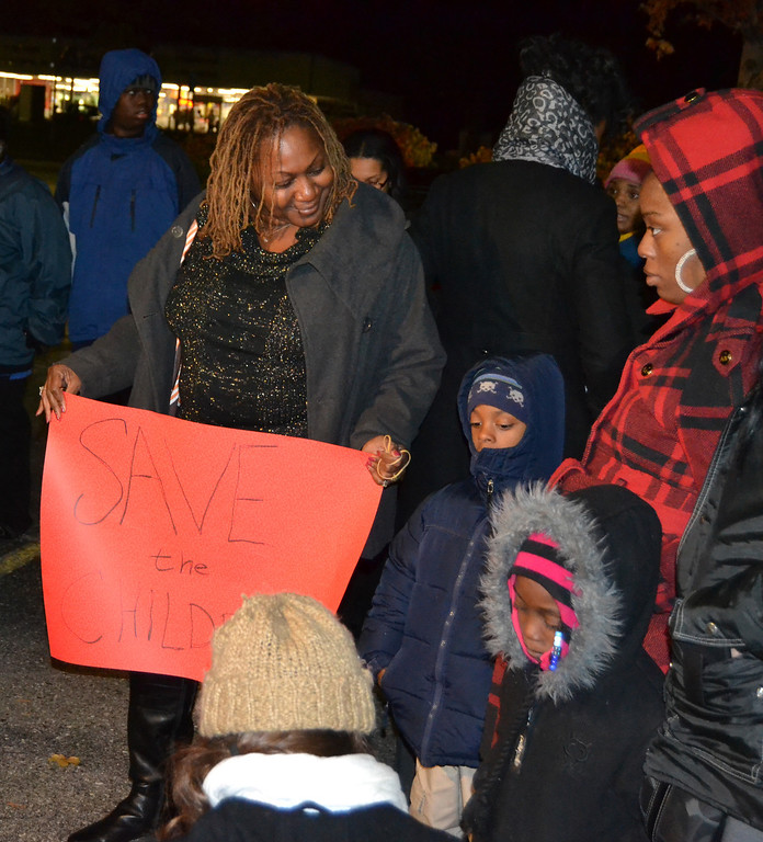 . Peggie Jarvis of Warren holds a �Save the Children� sign at a protest outside the Dearborn Heights police station Thursday evening.