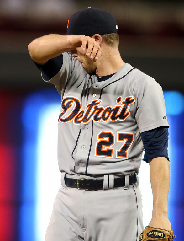 . Detroit Tigers shortstop Andrew Romine wipes his face as he gives up a solo home run to Minnesota Twins third baseman Trevor Plouffe while called upon to pitch in the eghth inning of a baseball game, Friday, Aug. 22, 2014, in Minneapolis. Romine also gave up a two-run home run to Twins\' Oswaldo Arcia moments earlier. The Twins won 20-6. (AP Photo/Jim Mone)