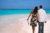 A couple walking along a beautiful tropical beach shoreline.