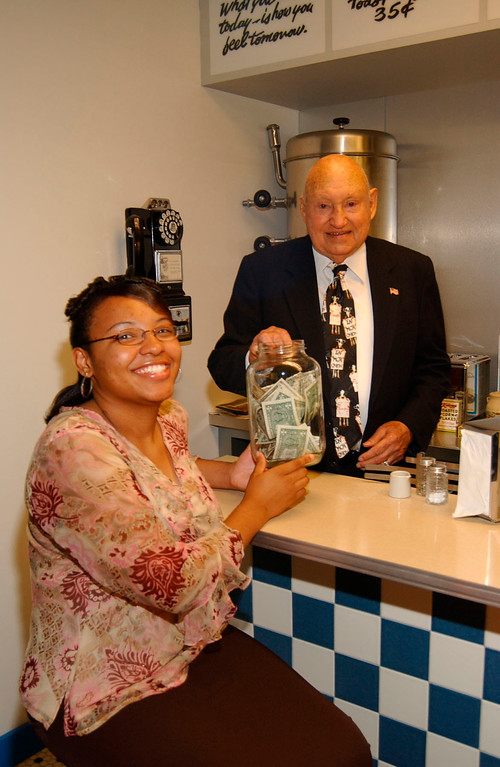 . Chick-fil-A founder and CEO Truett Cathy congratulates the chain\'s 20,000th Leadership Scholarship recipient Erica Lampkin.  They are seated at the original Dwarf Grill restaurant counter, now located in a museum at corporate headquarters, where 50 years ago Cathy placed a mayonnaise jar to help raise funds for an employee to attend college.  Since formally creating the scholarship program in 1973, Cathy has awarded $20 million to employees who have attended 2,138 educational institutions. (PRNewsFoto/Chick-fil-A)