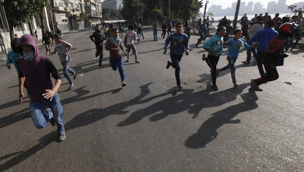 . Protesters, who oppose Egyptian President Mohamed Mursi, flee from riot police during clashes along Qasr Al Nil bridge, which leads to Tahrir Square in Cairo March 9, 2013.
