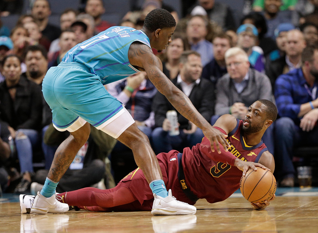 . Cleveland Cavaliers\' Dwyane Wade (9) looks to pass the ball as Charlotte Hornets\' Dwayne Bacon (7) defends during the first half of an NBA basketball game in Charlotte, N.C., Wednesday, Nov. 15, 2017. (AP Photo/Chuck Burton)