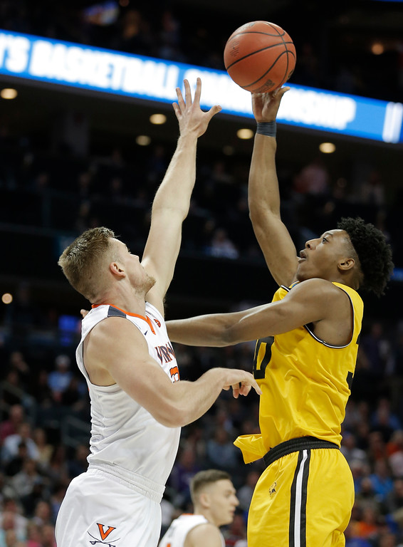 . UMBC\'s Daniel Akin, right, shoots over Virginia\'s Jack Salt during the first half of a first-round game in the NCAA men\'s college basketball tournament in Charlotte, N.C., Friday, March 16, 2018. (AP Photo/Bob Leverone)