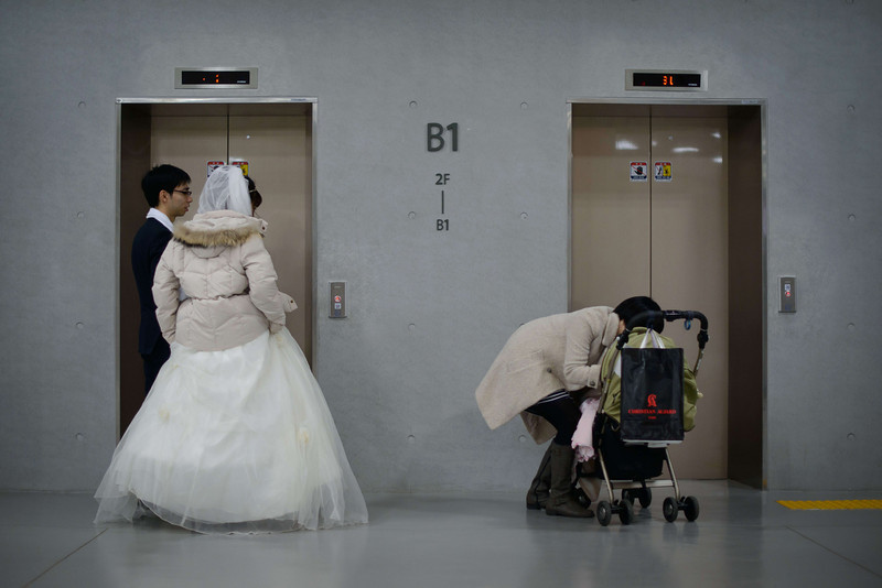 ". A newly-wed couple watch a mother and baby as they wait for an elevator at a mass wedding event held by the Unification Church in Gapyeong on February 12, 2014. Unification Church members forming 2500 couples from 52 countries were married in a mass wedding in South Korea -- only the second such event since the death of their ""messiah\"" and controversial church founder Sun Myung Moon. (ED JONES/AFP/Getty Images)"
