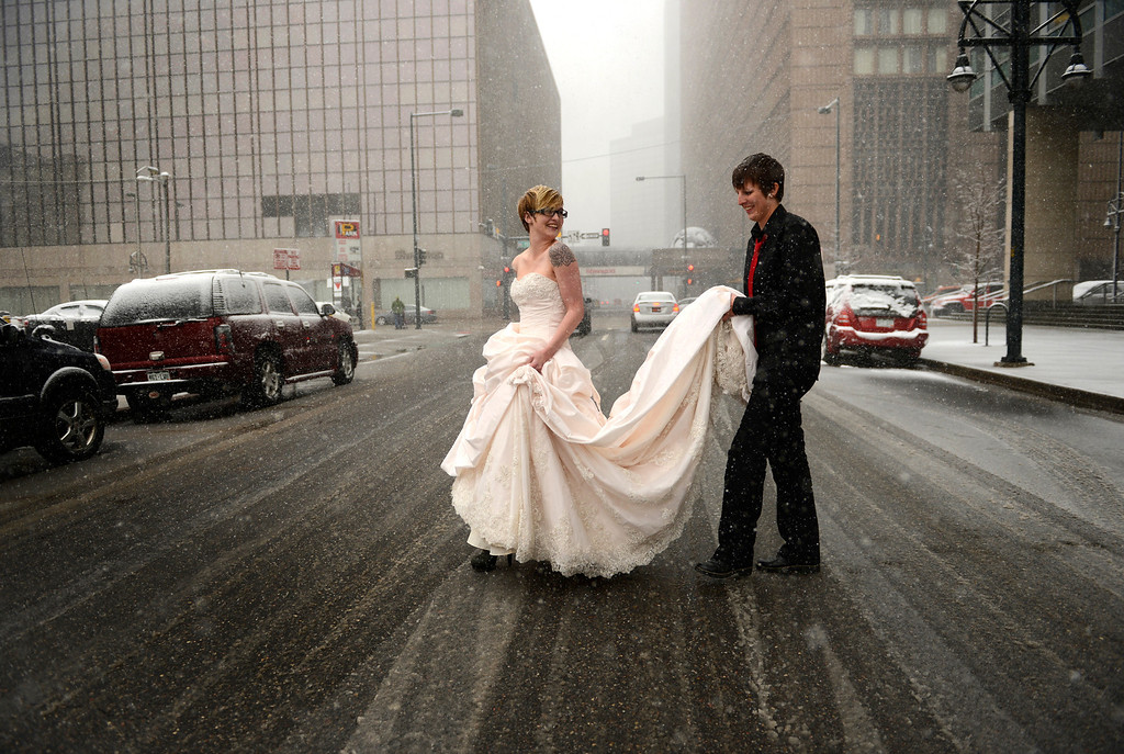 . Erin Ivie, 23, left, and her partner Kristyn Lindstrom, 25, leave to do wedding photos, outside in the snow, after their civil-union  ceremony in downtown Denver, May 01, 2013.  Hundreds of Colorado gay and lesbian couples put an official government seal on their relationships. (Photo By RJ Sangosti/The Denver Post)