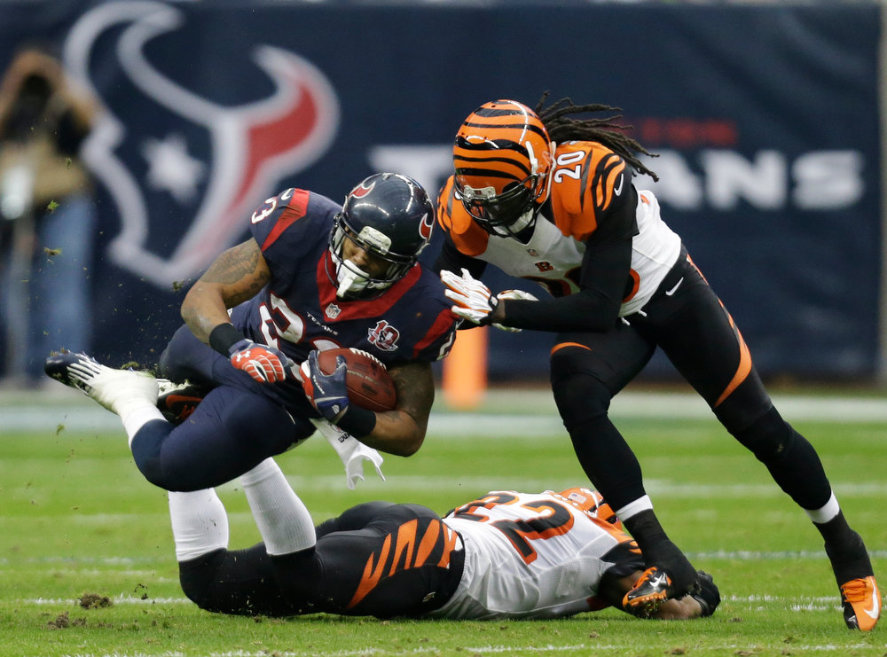. Houston Texans running back Arian Foster (23) is tackled by Cincinnati Bengals free safety Reggie Nelson (20) during the second quarter of an NFL wild card playoff football game Saturday, Jan. 5, 2013, in Houston. Cincinnati Bengals strong safety Nate Clements is underneath Foster. (AP Photo/Eric Gay)