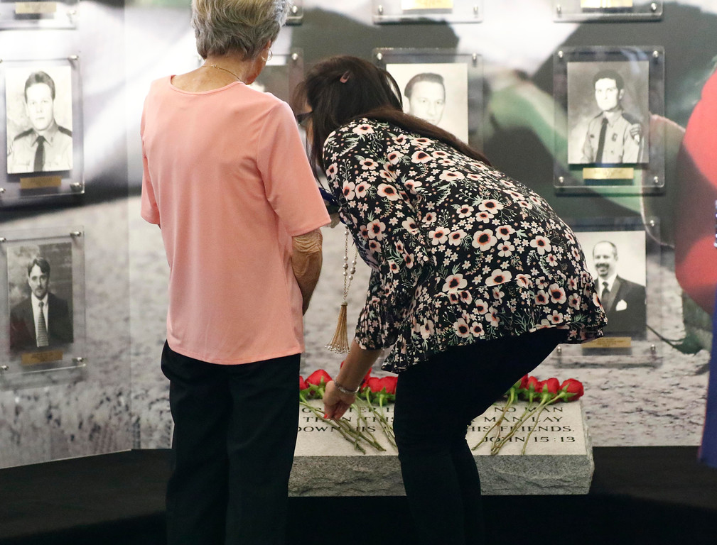 . Brenda Langham, widow of Mississippi Highway Patrol Trooper Billy Langham, who was killed in 1981, left, and an unidentified family member, leaves a rose on a memorial marker during the Mississippi Department of Public Safety Fallen Officers Memorial service, Tuesday, May 15, 2018, at department headquarters in Jackson, Miss. (AP Photo/Rogelio V. Solis)