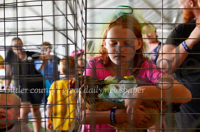 Lillian Wassam, 11, of Butler lifts her chicken to carry it to the judging table. Tanner Cole/Butler Eagle