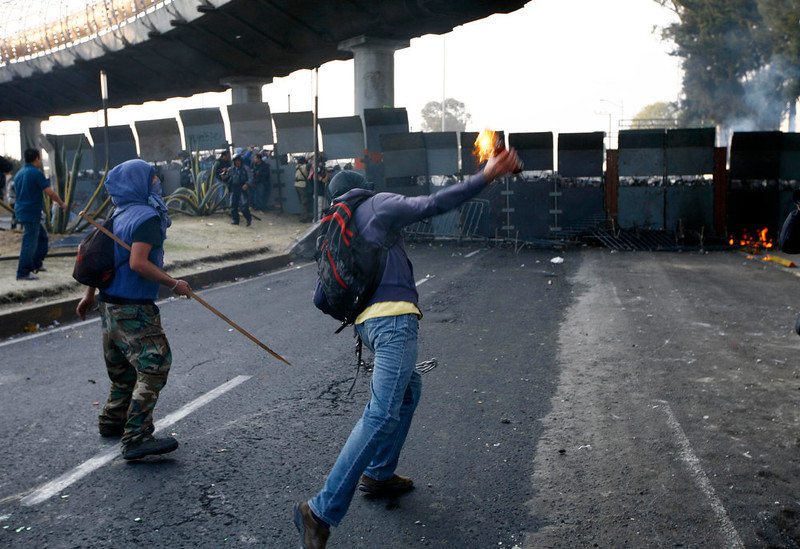 . A protestor throws a fire bottle over steel security barriers around the National Congress, where the swearing in of new Mexican President Enrique Pena Nieto will take place in Mexico City, Sunday, Dec. 1, 2012.  Pena Nieto took power at midnight in a symbolic ceremony and will formally take the oath of office Saturday morning after campaigning as the face of a new PRI _ a party that claims to be repentant and reconstructed after voted out of the presidency in 2000.(AP Photo / Marco Ugarte)