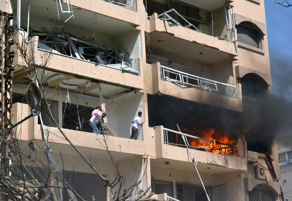 . Lebanese citizens remove debris from a damaged balcony at the site of an explosion in the northern city of Tripoli, Lebanon, Friday Aug. 23, 2013.  (AP Photo)