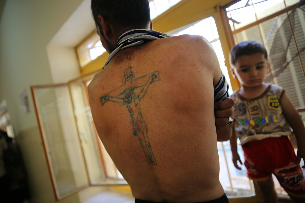 . ARBIL, IRAQ - JUNE 27: A displaced Iraqi Christian displays a tattoo of Christ on the Cross at Saint Joseph\'s church where he is living with hundreds of other Christians after having to flee their district on June 26, 2014 in Erbil, Iraq. Tens of thousands of people have fled Iraq\'s second largest city of Mosul after it was overrun by ISIS (Islamic State of Iraq and Syria) militants. Many have been temporarily housed at various IDP camps around the region including the area close to Erbil, as they hope to enter the safety of the nearby Kurdish region. Christians, Shiites and Kurdish Iraqis have received the brunt of the violence from the militants.  (Photo by Spencer Platt/Getty Images)