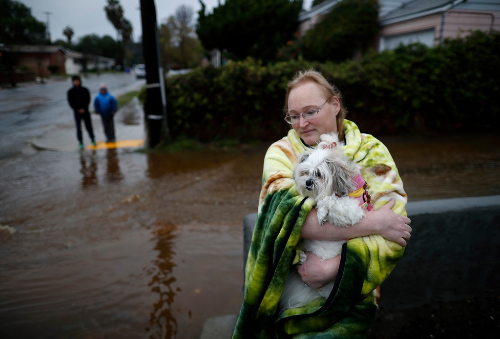 . A woman who gave her name as Julie holds her dog Shana as they wait outside of her office after rainwater flooded the street Friday, Jan. 20, 2017, in San Diego. Flash flood warnings have been issued in various places in Southern California Friday as the area is pounded by wind and rain from the second of a series of storms this week. (AP Photo/Gregory Bull)