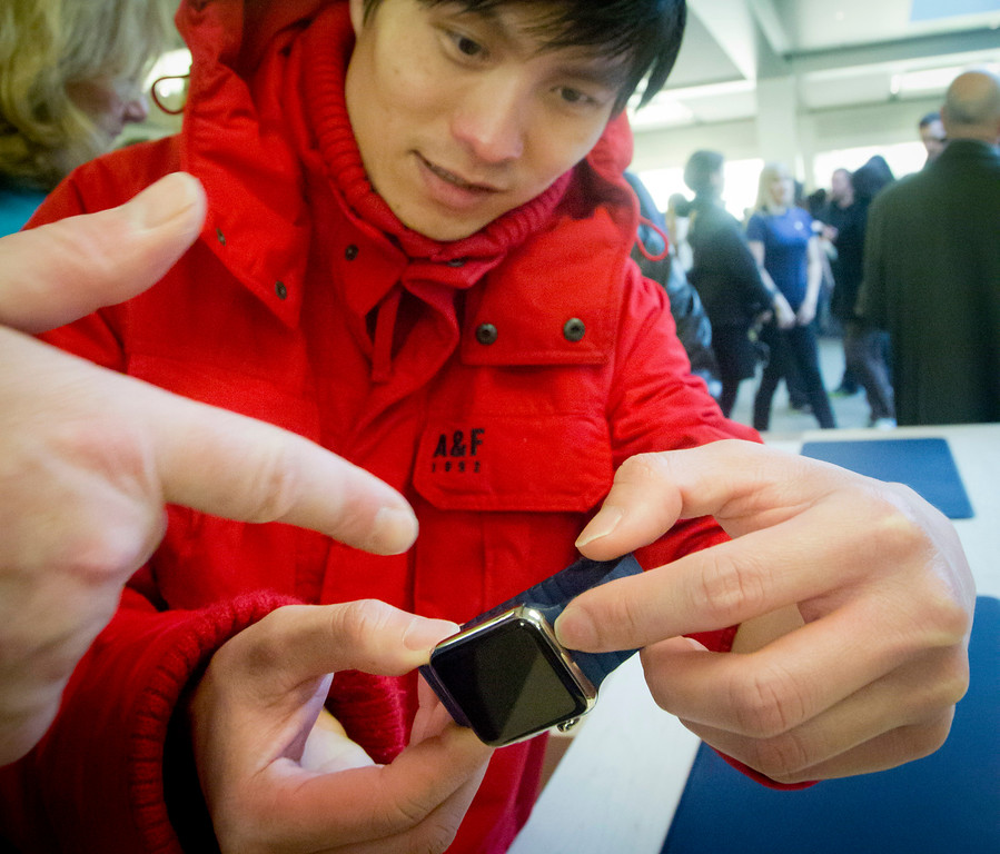 . Ricky Lea examines Apple\'s new watch, which could only be bought as a pre-order online, Friday, April 10, 2015, in New York.  The first new gadget under CEO Tim Cook is selling in eight countries and Hong Kong, with shipments scheduled to start April 24. (AP Photo/Bebeto Matthews)
