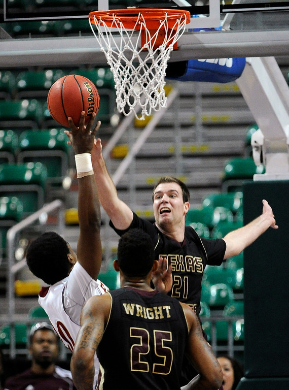 . Texas State\'s Matt Staff (21) attempts to block a shot by Denver\'s Royce O\'Neale (20) during the fist half of a Western Athletic Conference tournament NCAA college basketball game on Thursday, March 14, 2013, in Las Vegas. (AP Photo/David Becker)