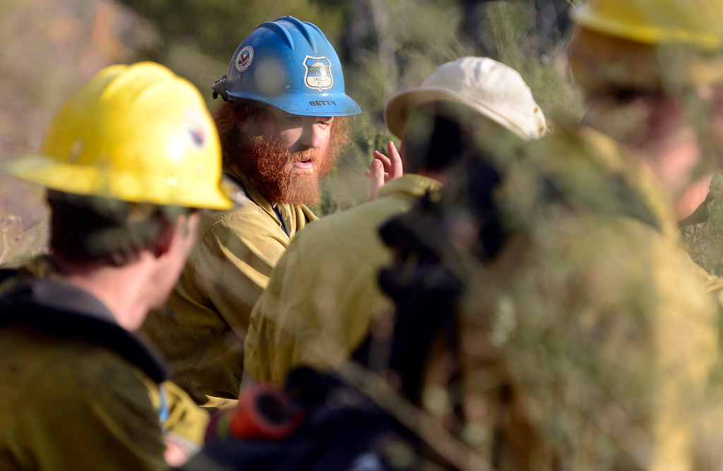 . Lassen National Forest crew boss Kyle Betty speaks with other fire crew while watching helicopter water drops at a vantage point across the valley from Pfeiffer Ridge in Big Sur, Calif. on Thursday December 19, 2013. (Photo David Royal/ Monterey County Herald)
