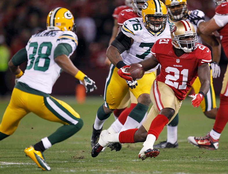 . San Francisco 49ers Frank Gore (R) runs between Green Bay Packers Tramon Williams (L) and Mike Daniels (C) in the first quarter during their NFL NFC Divisional playoff football game in San Francisco, California January 12, 2013. REUTERS/Robert Galbraith
