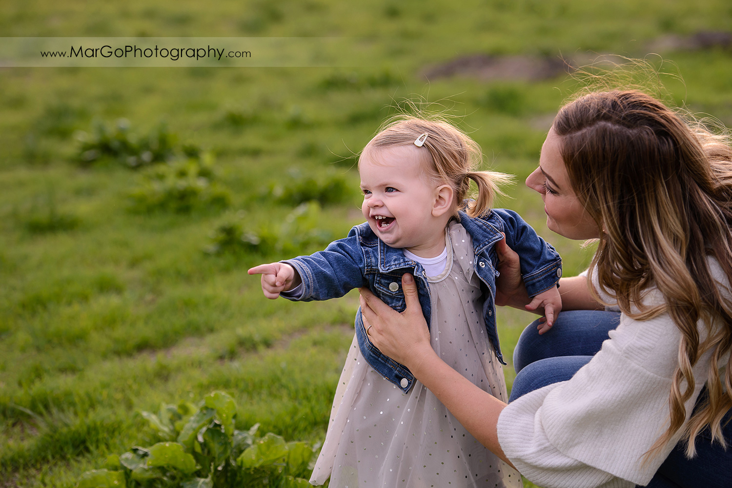 little girl in white dress and jeans jacket and woman in white blouse and jeans laughing during family session at San Jose Martial Cottle Park