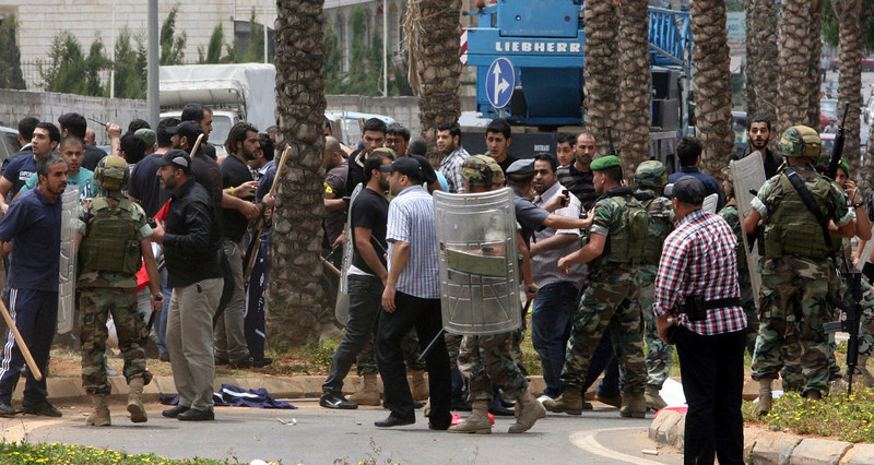 . Lebanese soldiers and Hezbollah supporters are seen gathered in front of the Iranian embassy in Beirut June 9, 2013. An unarmed Lebanese protester, a member of a small crowd demonstrating against the backing of Iran and its Hezbollah ally for Syrian President Bashar al-Assad, was killed on Sunday by gunfire in front of the embassy in Beirut, Lebanese security officials said.    REUTERS/ Stringer