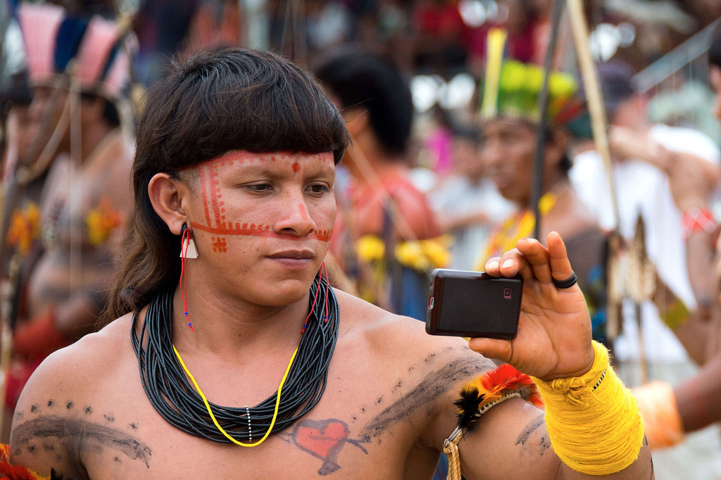 . An indigenous man records participants of the bow and arrow competition with his mobile phone during the XII International Games of Indigenous Peoples in Cuiaba, Mato Grosso state, Brazil on November 12, 2013. 1AFP PHOTO / Christophe SIMON/AFP/Getty Images