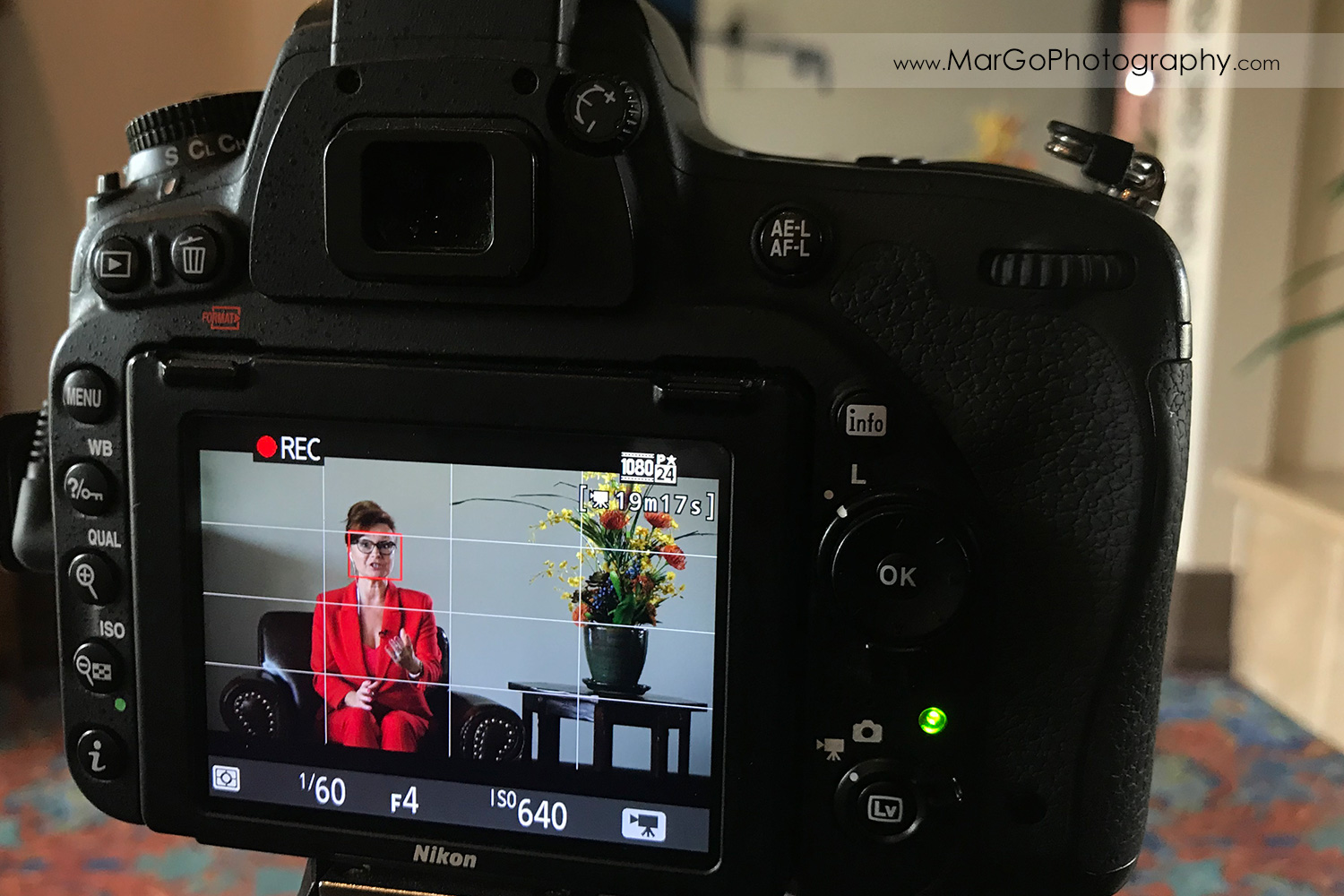 behind the scenes of indoor filming woman speaker in red suit sitting on the brown chair - camera LCD screen