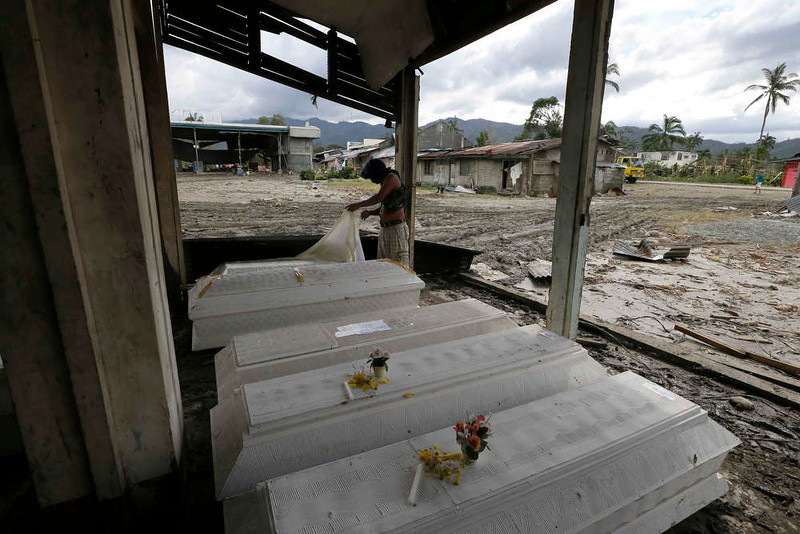 . Eddie Jotojot checks the coffin of his son Ejiedev who was killed at the height of Tuesday\'s typhoon Bopha at New Bataan township, Compostela Valley in southern Philippines Saturday Dec. 8, 2012. Search and rescue operations following a typhoon that killed nearly 600 people in the southern Philippines have been hampered in part because many residents of this ravaged farming community are too stunned to assist recovery efforts, an official said Saturday. (AP Photo/Bullit Marquez)