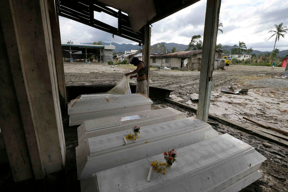 Description of . Eddie Jotojot checks the coffin of his son Ejiedev who was killed at the height of Tuesday\'s typhoon Bopha at New Bataan township, Compostela Valley in southern Philippines Saturday Dec. 8, 2012. Search and rescue operations following a typhoon that killed nearly 600 people in the southern Philippines have been hampered in part because many residents of this ravaged farming community are too stunned to assist recovery efforts, an official said Saturday. (AP Photo/Bullit Marquez)