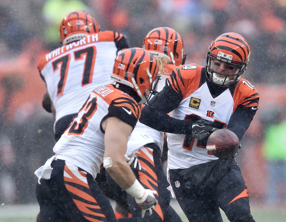 . Cincinnati Bengals quarterback Andy Dalton (14) hands the ball off in the first half of an NFL football game against the Cleveland Browns, Sunday, Dec. 11, 2016, in Cleveland. (AP Photo/David Richard)