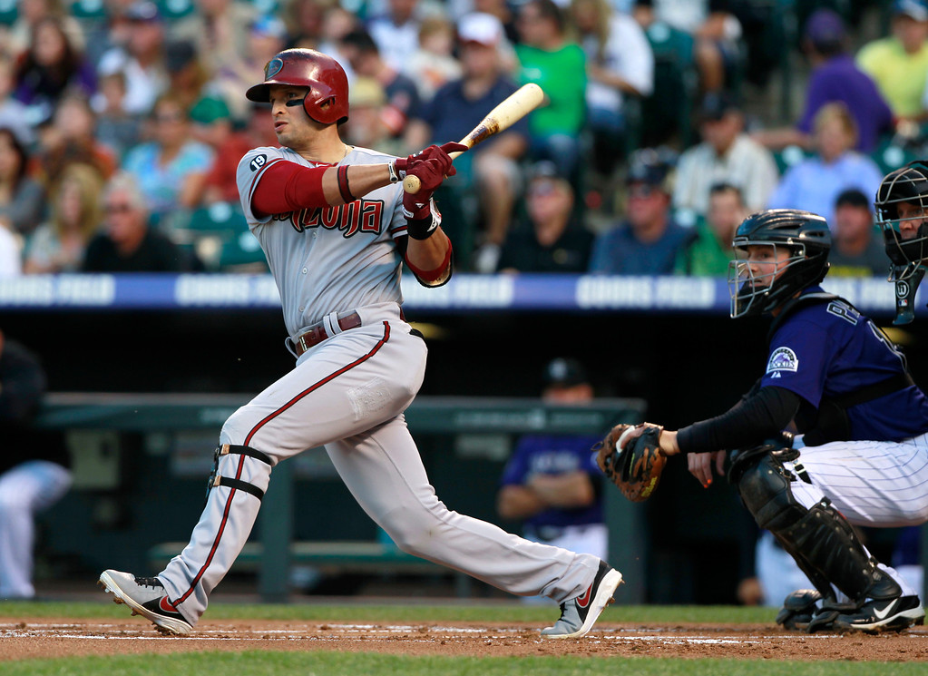 . Arizona Diamondbacks\' Martin Prado, left, follows the flight of his RBI double as Colorado Rockies catcher Jordan Pacheco watches during the first inning of a baseball game in Denver on Saturday, Sept. 21, 2013. (AP Photo/David Zalubowski)