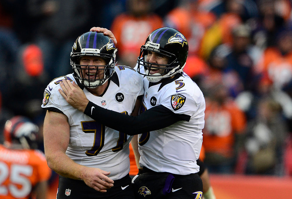 Description of . Baltimore Ravens quarterback Joe Flacco (5) celebrates a touchdown pass with Baltimore Ravens center Matt Birk (77) in the second quarter. The Denver Broncos vs Baltimore Ravens AFC Divisional playoff game at Sports Authority Field Saturday January 12, 2013. (Photo by AAron  Ontiveroz,/The Denver Post)