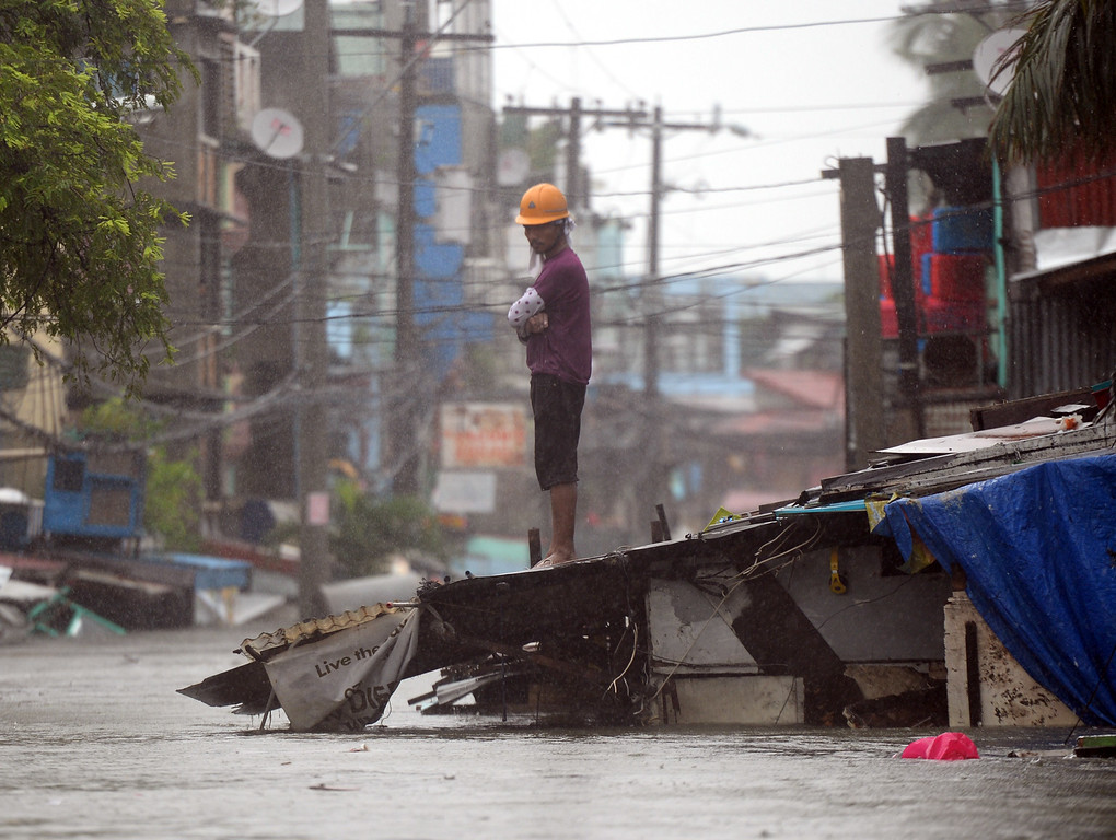 . A resident stands on top of the roof of his submerged house as heavy rains brought about by Tropical Storm Fung-Wong flooded homes in Manila on September 19, 2014. TED ALJIBE/AFP/Getty Images