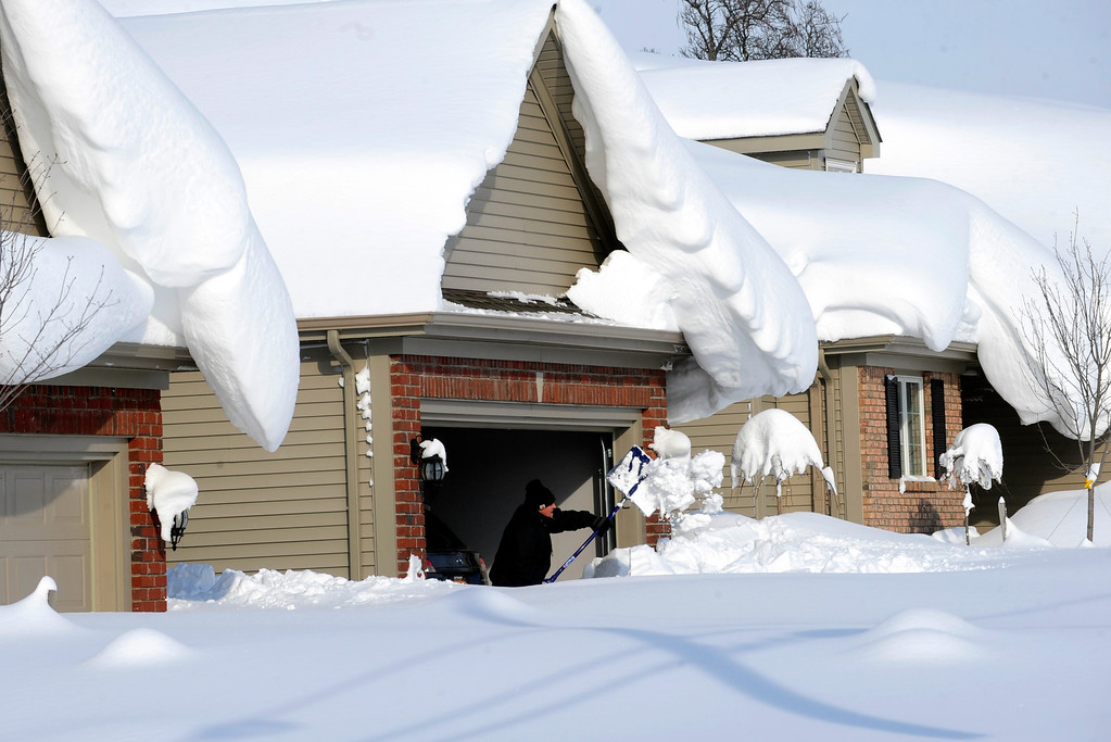 . Snowdrifts create a beautiful setting as a man tries to dig out his driveway on Bowen Rd in Lancaster, N.Y. Wednesday, Nov. 19, 2014. A lake-effect snow storm dumped over five feet of snow in areas across Western New York. Another two to three feet of snow is expected in the area, bringing snow totals to over 100 inches, almost a years\' worth of snow in three days.  (AP photo/Gary Wiepert)
