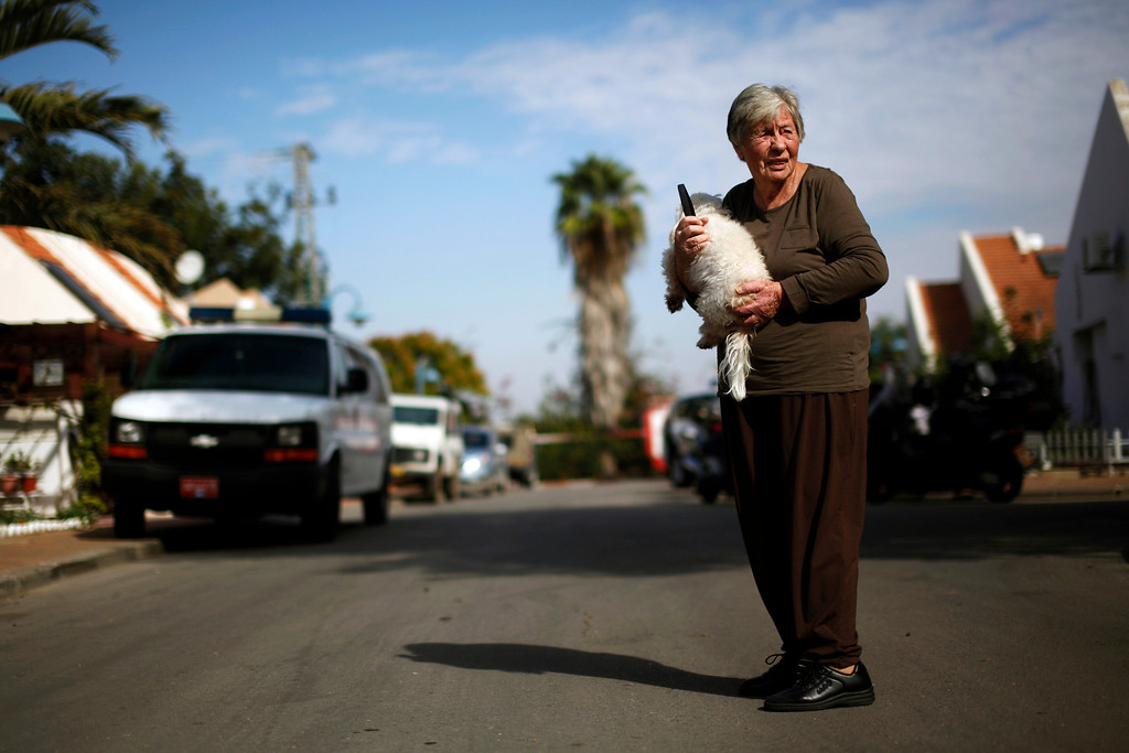 . An Israeli woman holds a dog as she stands near the scene where a rocket landed in Arugot, east of Ashdod November 21, 2012. REUTERS/Amir Cohen