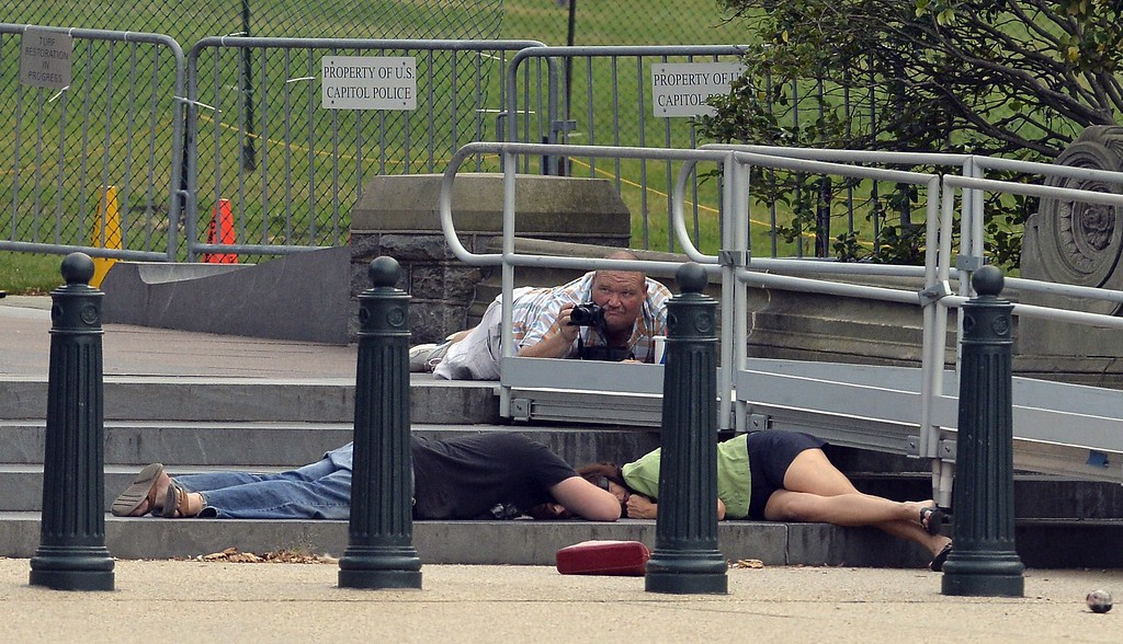 """. People take cover as gun shots were being heard at the US Capitol in Washington, DC, on October 3, 2013. The US Capitol was placed on security lockdown Thursday after shots were fired outside the complex, senators said. \""""Shots fired outside the Capitol. We are in temporary lock down,\"""" Senator Claire McCaskill said on Twitter. Police were seen running within the Capitol building and outside as vehicles swarmed to the scene. AFP Photo/Jewel SAMAD/AFP/Getty Images"""