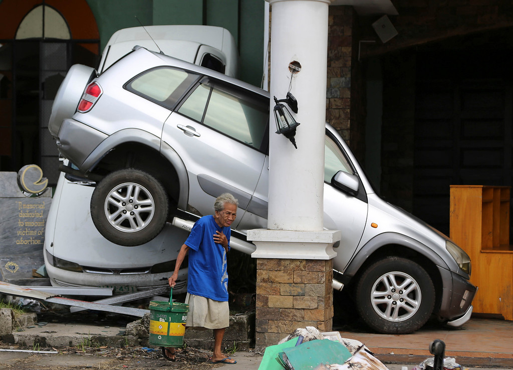 . An old woman survivor walks past toppled cars outside a church at typhoon-hit Tacloban city, Leyte province, central Philippines on Saturday, Nov. 16, 2013. T (AP Photo/Aaron Favila)