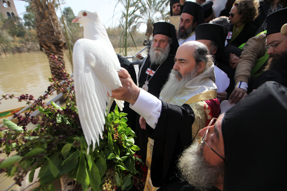 Description of . JERICHO, ISRAEL - JANUARY 18:  Greek Orthodox Patriarch Theophilos III of Jerusalem holds a white dove and prays during a traditional Epiphany ceremony at the baptismal site of Qasr el-Yahud near the West Bank city of Jericho on January 18, 2013. Thousands of Orthodox pilgrims come every year to the celebrate where it is believed that Jesus was baptised. (Photo by Abir Sultan - Pool/Getty Images)