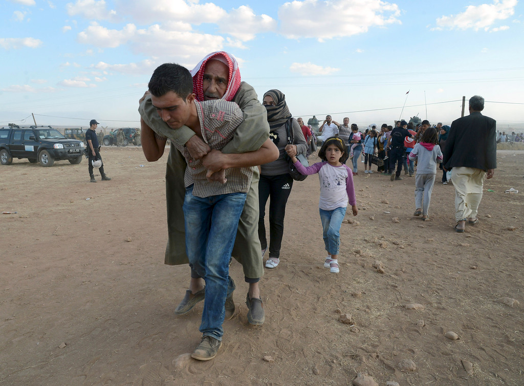 . A Syrian refugee carries a sick person at the border in Suruc, Turkey, late Saturday, Sept. 20, 2014.(AP Photo)