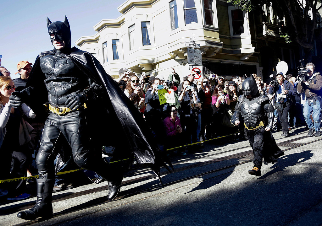 ". Miles Scott, dressed as Batkid, right, runs with Batman after saving a damsel in distress in San Francisco, Friday, Nov. 15, 2013. San Francisco turned into Gotham City on Friday, as city officials helped fulfill Scott\'s wish to be ""Batkid.\"" Scott, a leukemia patient from Tulelake in far Northern California, was called into service on Friday morning by San Francisco Police Chief Greg Suhr to help fight crime, The Greater Bay Area Make-A-Wish Foundation says. (AP Photo/Jeff Chiu)"