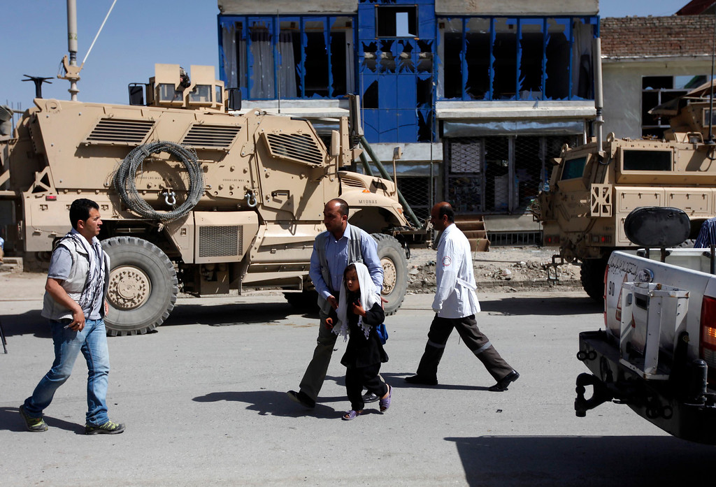 . A man helps a school girl at the site of a suicide attack in Kabul May 16, 2013.  REUTERS/Mohammad Ismail